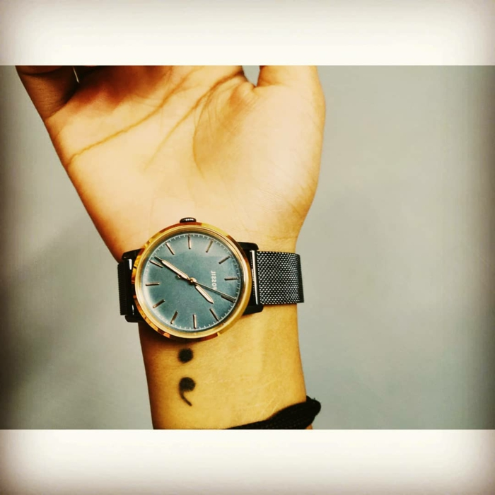 Schwarzes Semicolon Tattoo am Arm und eine grüne Uhr, tattoo psychische störung