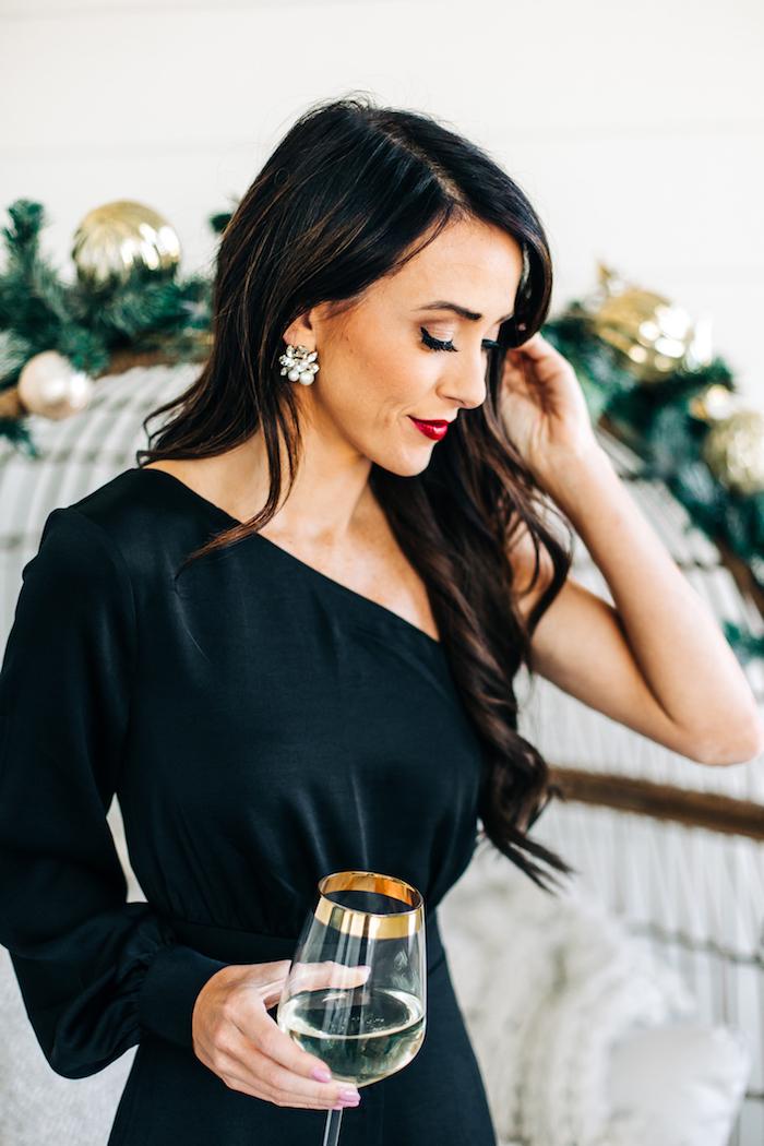 Schwarzes Cocktail Kleid mit einem Ärmel, offene gewellte Haare, seitlich getragen, silberne Ohrringe mit Kristallen