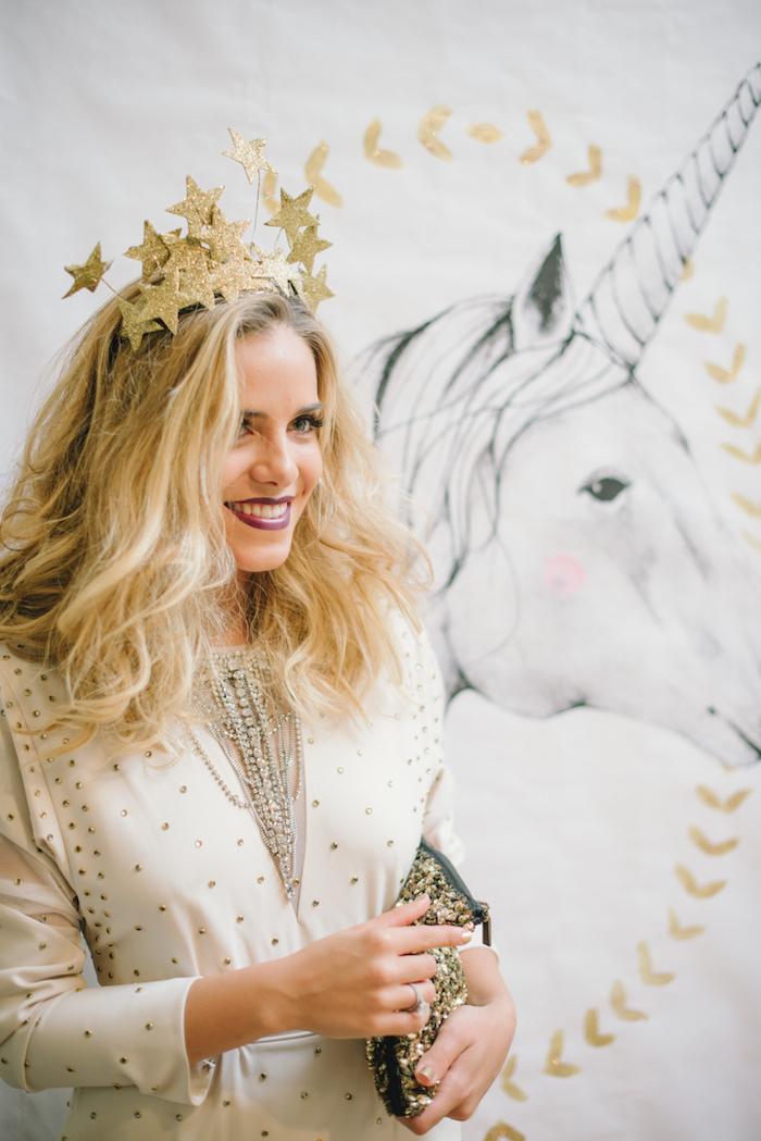 Cooler Silvester Look, weißes Outfit mit kleinen Perlen, schwarze Clutch mit goldenen Elementen, Tiara mit Sternen
