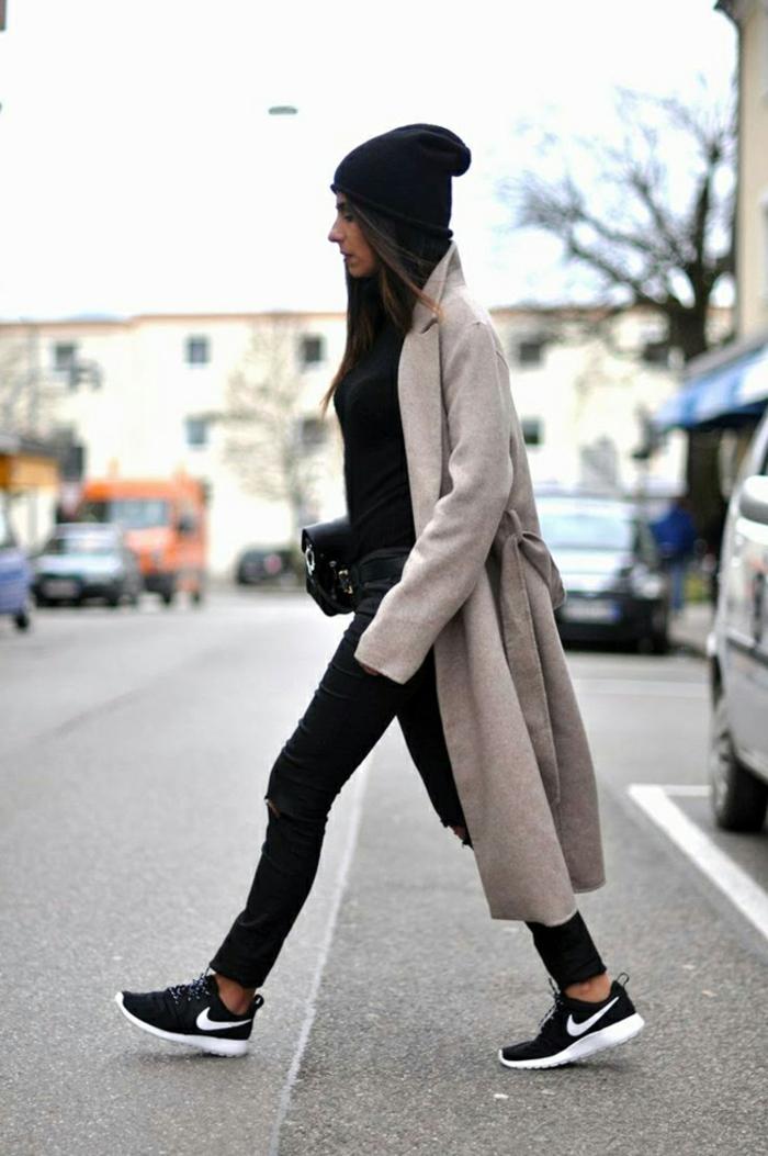 Bequem angezogene Frau in Jeans und Sneakers in Schwarz, mit Mütze und schwarzer Tasche
