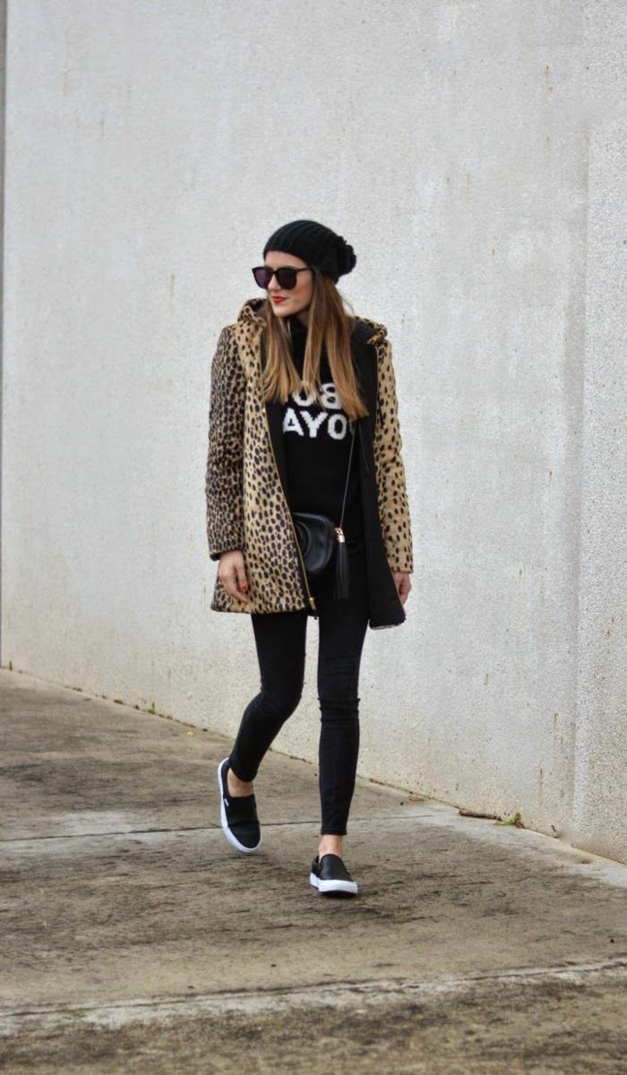 Frau im Mantel mit Leopardenmuster, schwarze skinny Jeans, Mütze und kleine Handtasche