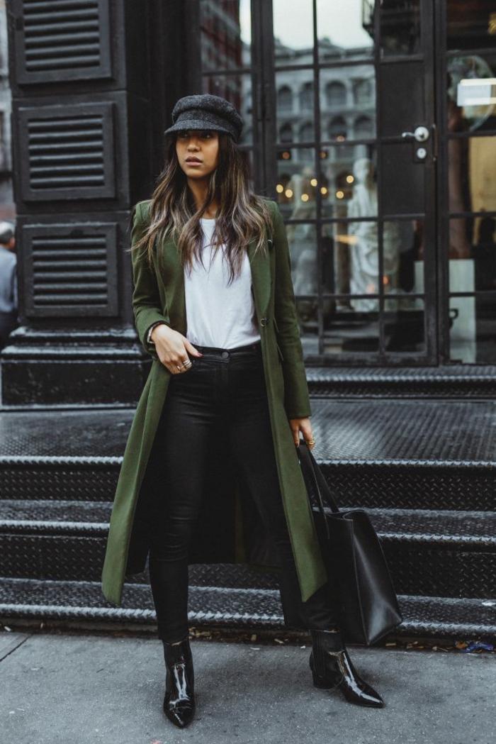 Stylishe Frau in einem grünen Mantel, Jeans und Stiefel in Schwarz, mit Hut