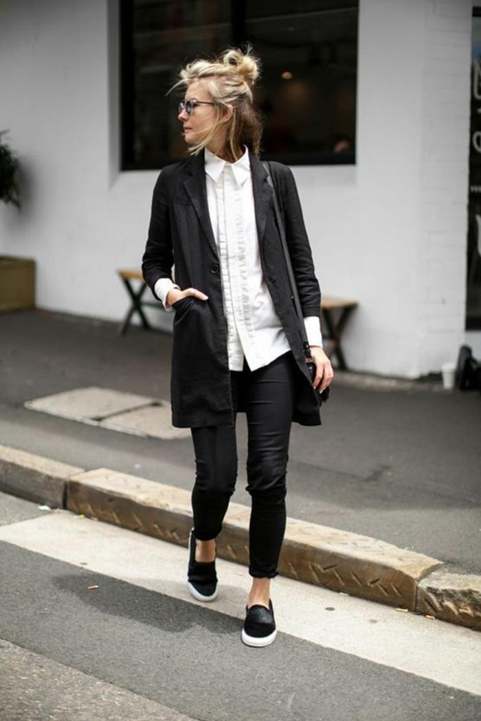 Sportlich angezogene Dame mit langem Mantel, hochgeknöpfter Bluse und schwarzen Jeans, casual dress code