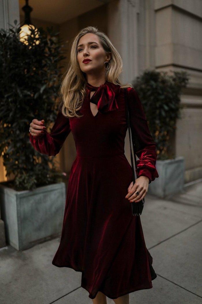 Elegantes Kleid in Bordeaux mit langen Ärmeln, offene blonde Haare mit seitlichem Scheitel
