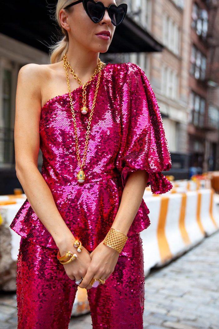 Violettes Glitzer Outfit, Oberteil mit einem Ärmel, goldener Schmuck, herzförmige Sonnenbrille