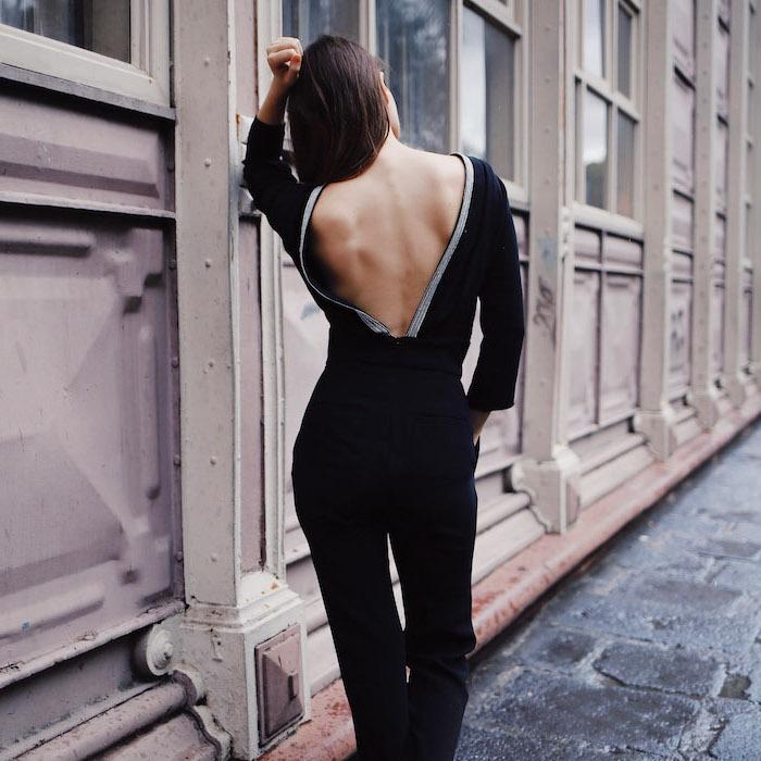 Schwarzer Jumpsuit rückenfrei mit weißer Kante, mit langen Ärmeln, offene glatte Haare