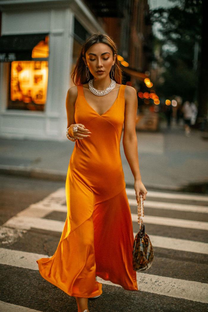 Elegantes Satinkleid in Orange, offene Balayage Haare, Halskette mit Kristallen