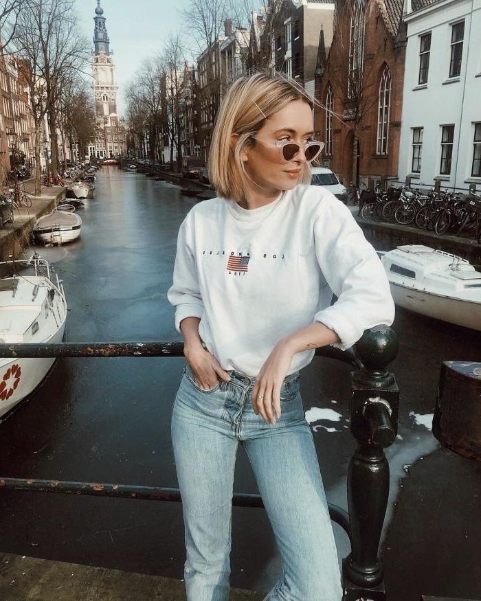stylische frau in jeans und weißem sweatshirt mit pinken sonnenbrillen, modische kurzhaarfrisuren, blonde Haare