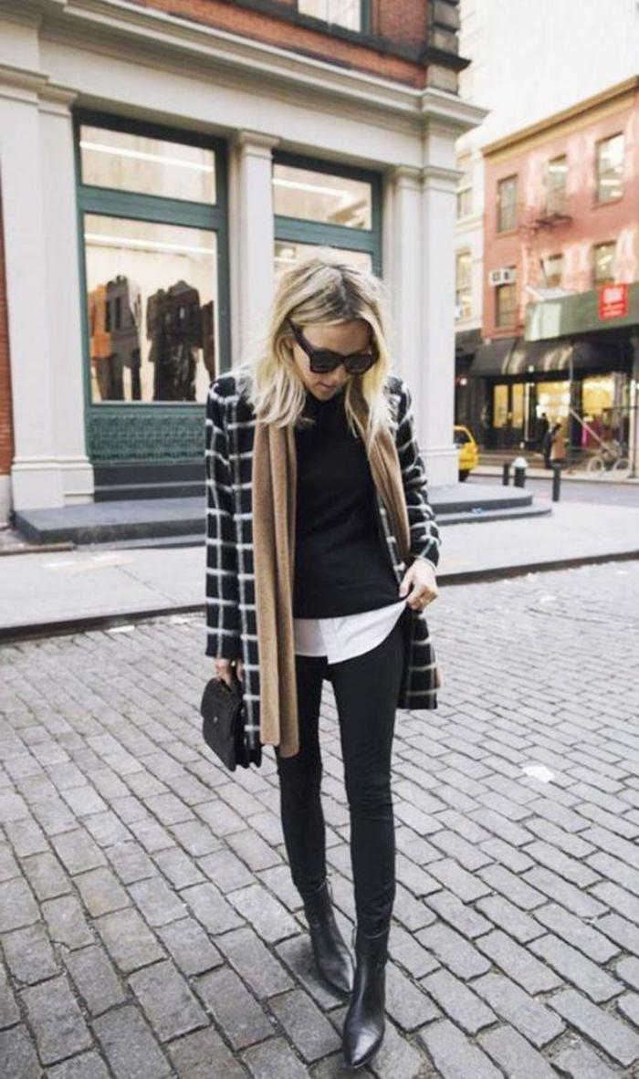 Dame in Jeans in Schwarz, mit einem karierten Mantel und Stiefel aus Leder