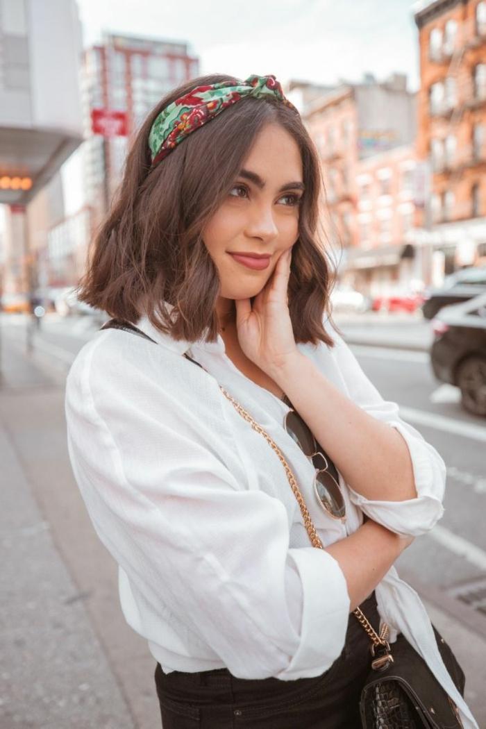 Street Style Fotografie, Brünette Frau mit buntem Haarreif, weiße Bluse und schwarze Jeans, schwarze Tasche mit goldener Kette, Haarfrisuren kurz