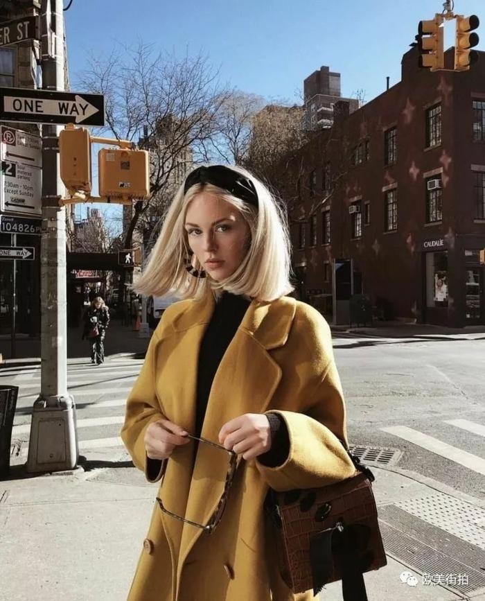 damenfrisuren kurz, blonde Haare, frau im gelben Mantel und braune Tasche, schwarzes Haarreif, street style Fotografie