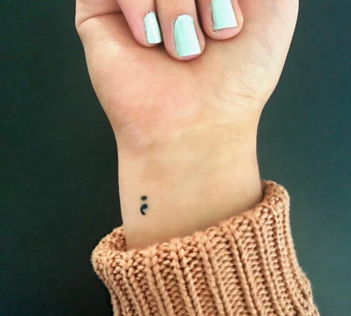 Kleines Semicolon Tattoo am Arm einer Frau mit bläulichem Nagellack, semikolon tattoo bedeutung