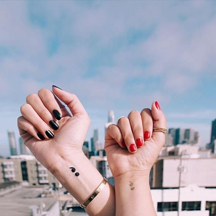 Zwei Hände mit Semicolon Tattoos, eine mit schwarzem, die andere mit rotem Nagellack, depression tattoos