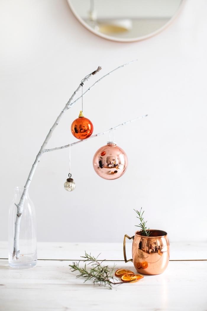 tischdeko weihnachten, zweig dekroiert mit chrimierten weihnachtskugeln, tisch festlich dekorieren