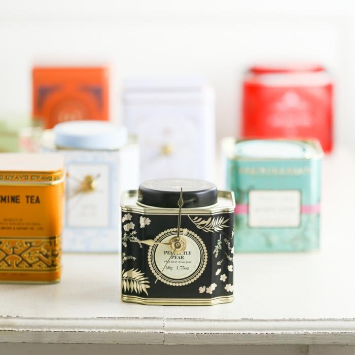 Kleine Uhr aus alte Teedose in schwarz, andere Uhren im Hintergrund in verschiedene Farben, Geschenk Oma Tipps, Geschenkideen für Oma