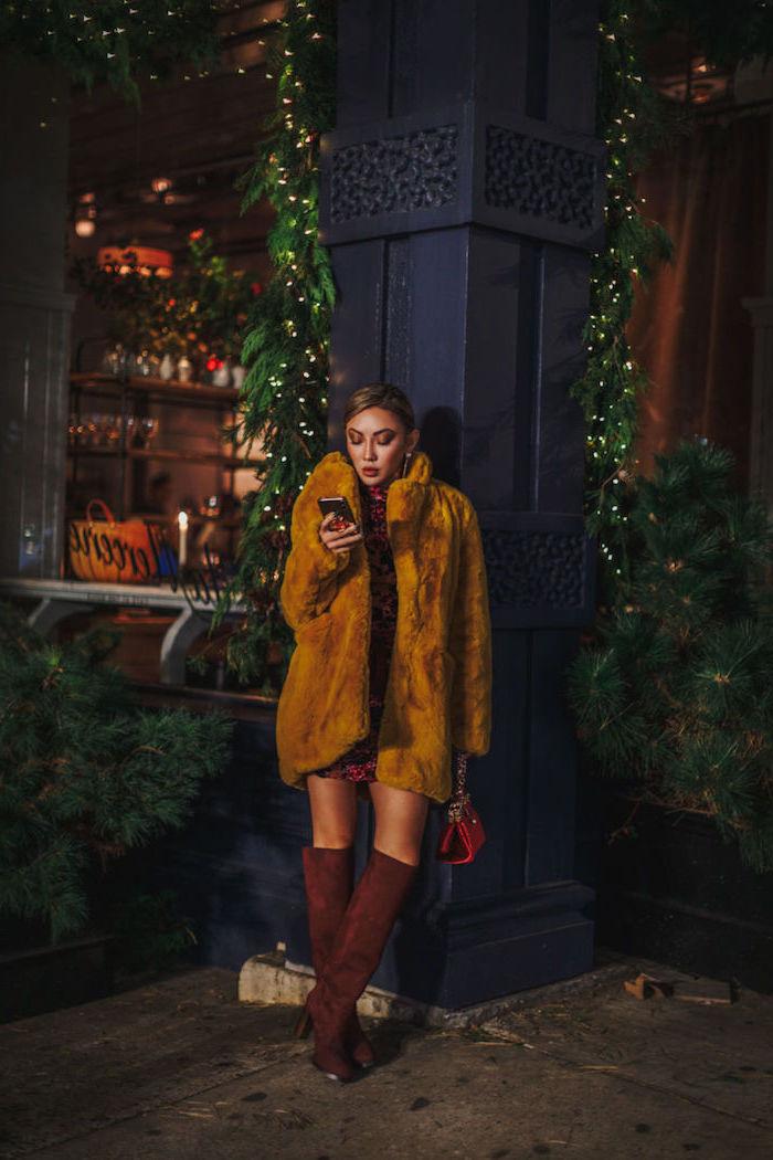 Pelzmantel in Farbe Senf, braune Stiefel, rote Clutch, gebundene Haare, Silvester Outfit