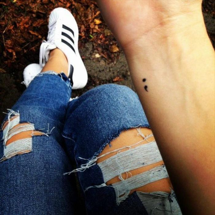Dezentes Semicolon Tattoo auf einer Hand. project semicolon, zerrissene Jeans, weiße sneakers