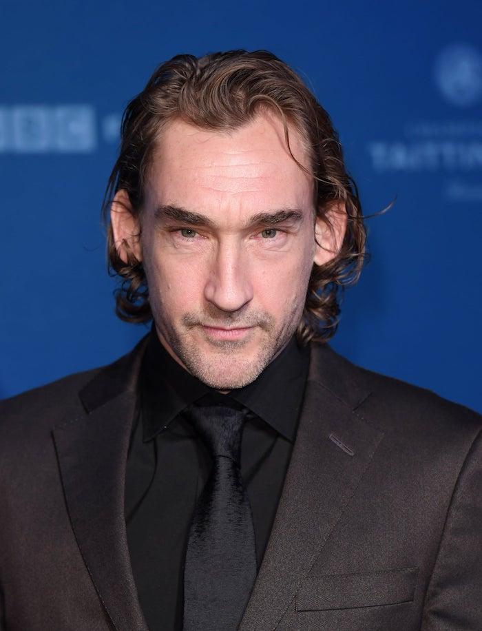 ein mann mit einem schwarzen hemd und einer schwarzen krawatte, der schauspieler joseph mawle, der hauotcast für die amazon seire der herr der ringe