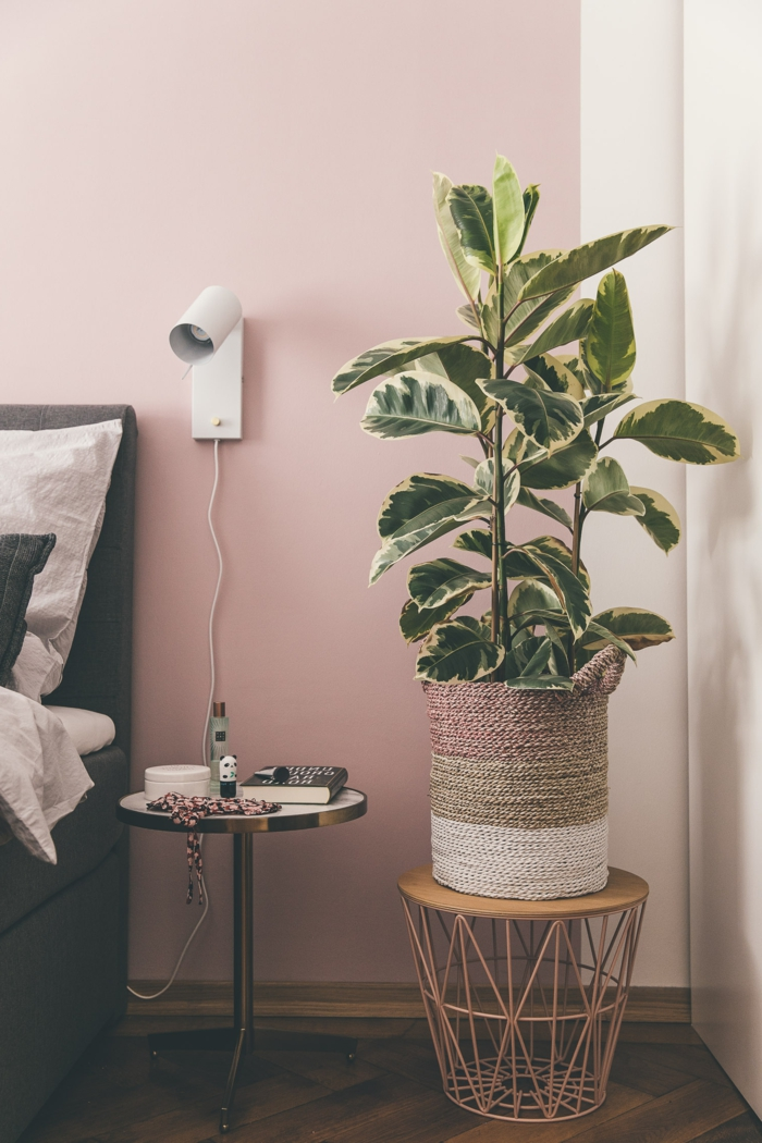 Schlafzimmer rosa grau, runder Nachttisch mit Gegenständen, graues Bett mit Bettwäsche in weiß, große grüne Pflanze und Korbtisch