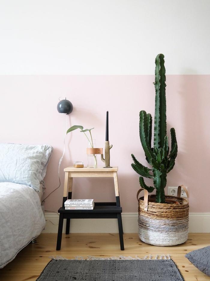 Wand bemalt in zwei Farben, Schlafzimmer rosa grau, Teppich und Lampe in grau, großer Kaktus als Dekoration in einem Weidenkorb