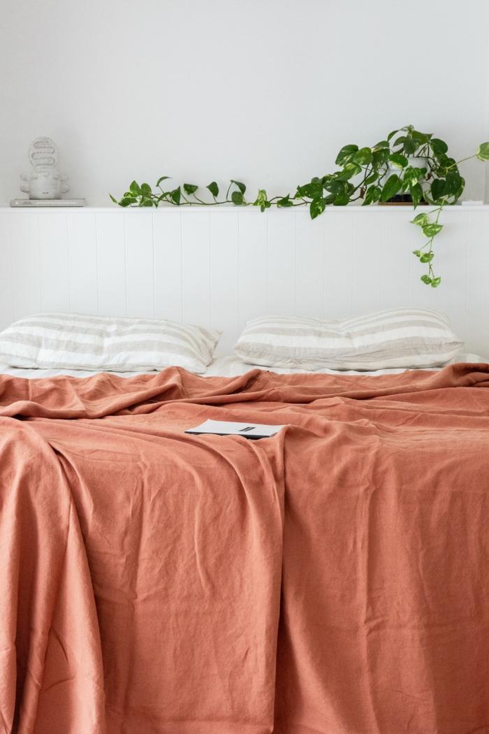 Großes Bett mit Bettwäsche in altrosa Farbe, zwei weiße gestreifte Kissen, Aktuelle Wohnraum Farben, Grüne Pflanze im Hintergrund