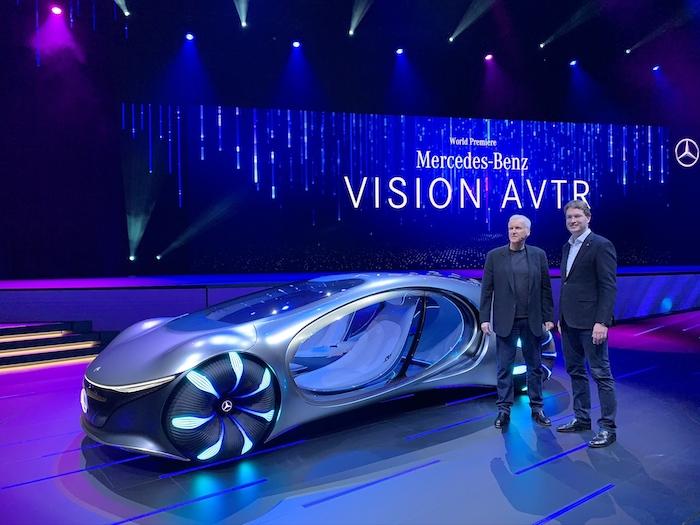 eine bühne mit dem neuen auto mercedes benz vision avtr, das von dem film avatar inspiriert wurde, und zwei männer, der reigisseru james cameron