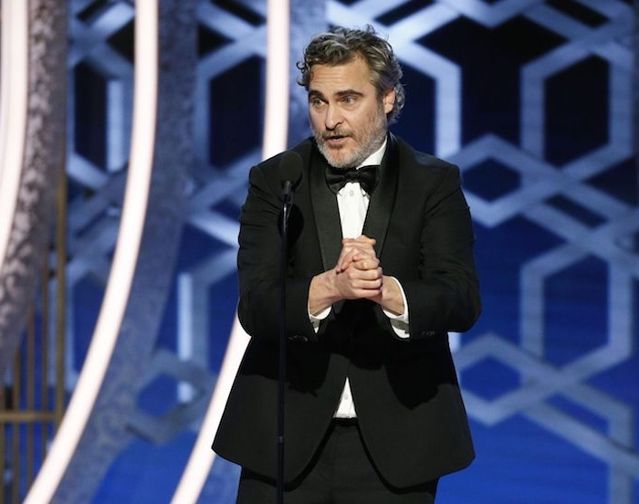 ein mann mit einem schwarzen anzug und hemd und fliege, der schauspieler joaquin phoenix, golden globe awards 2020
