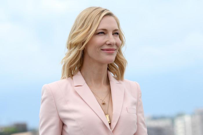 blauer himmel und eine frau mit blondem haar, pinkem sakko und goldenen halsketten, die schauspielerin cate blanchett