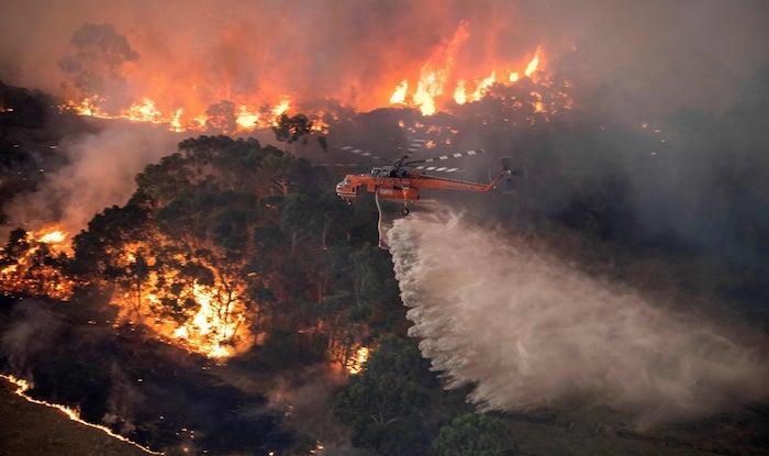 ein großer oranger fliegender hubschrauber und wasser, die buschbrände in australien, ein wald und feuer