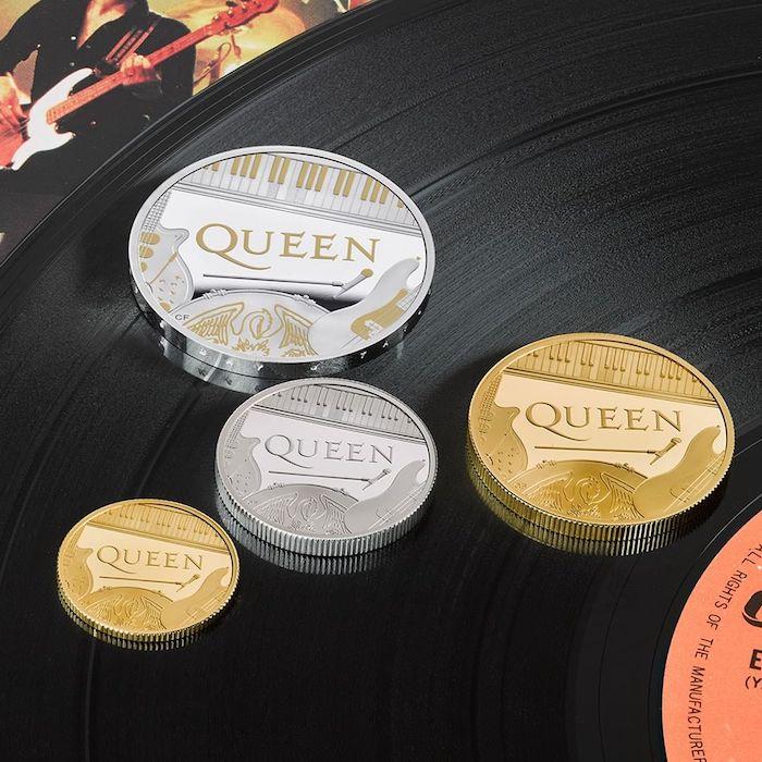 vier kleine und große münzen mit dem logo von der britischen band queen, ein Mikrofon und ywei gitarren und ein fl[gel