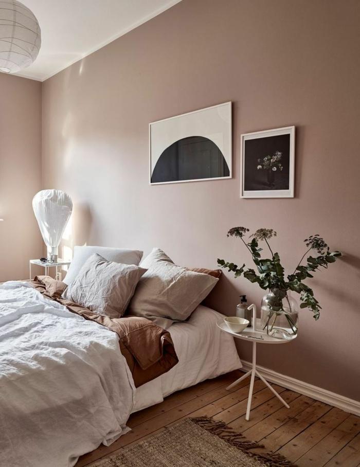 Aktuelle Wohnraumfarben fürs Schlafzimmer, Wandfarbe altrosa, Bett mit Bettwäsche in beige, schwarz weiße Bilder an die Wand. runder Tisch,
