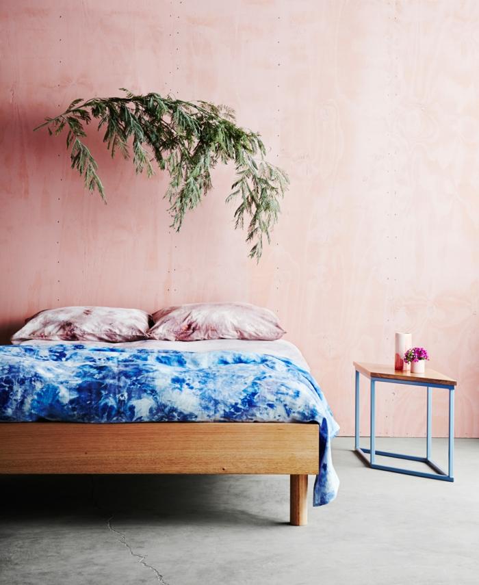 Schlafzimmer rosa grau, großes Bett mit blauen Bettwäschen, Kissen in pink, grüne Pflanze, rechteckiger Tisch