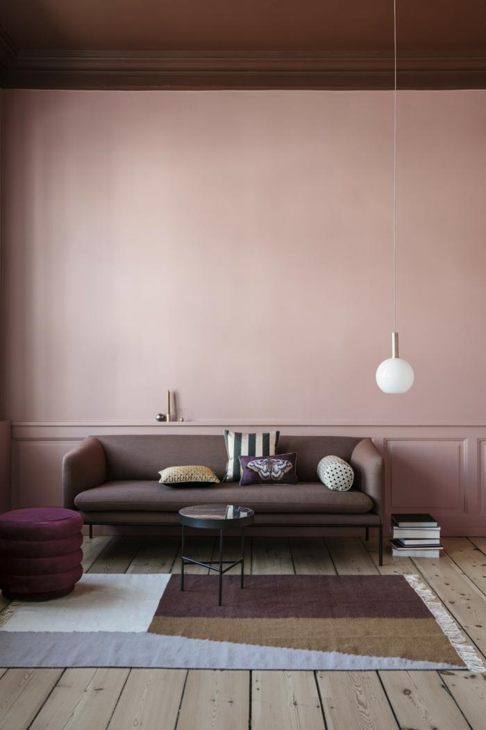 rosa Farbe, Grafischer Teppich in verschiedenen Farben, dunkler Couch, Wandfarbe Inspiration in altrosa, Hängende Lampe, Boden aus Holz,