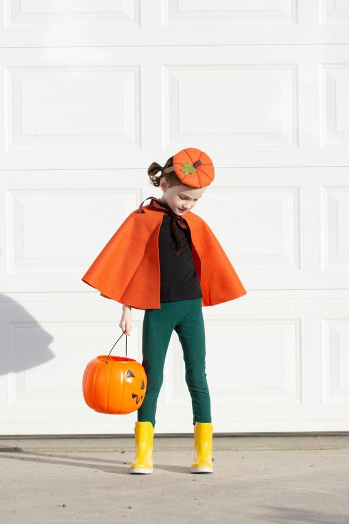 Faschingskostüme für Kinder, Kürbis Kostüm mit Umhang und Hut in orange mit grünen Hosen und gelben Schuhen, Mädchen hält ein Kürbiskopf