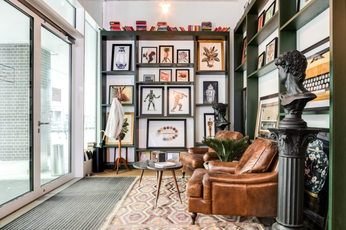 Zwei große Sessel aus Leder, Wand mit vielen Bildern mit Rahmen, zwei runde Tische, Wandbilder Wohnzimmer,