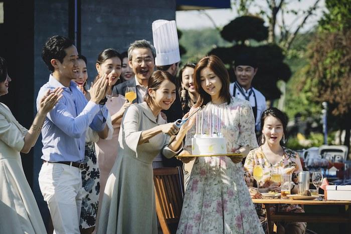 tisch und stuhl aus holz, eine szene aus dem südkoreanischen film parasite, eine garenparty mit vielen menschen, eine frau mit kleid mit blumen, eine junge frau mit weiner weißen torte