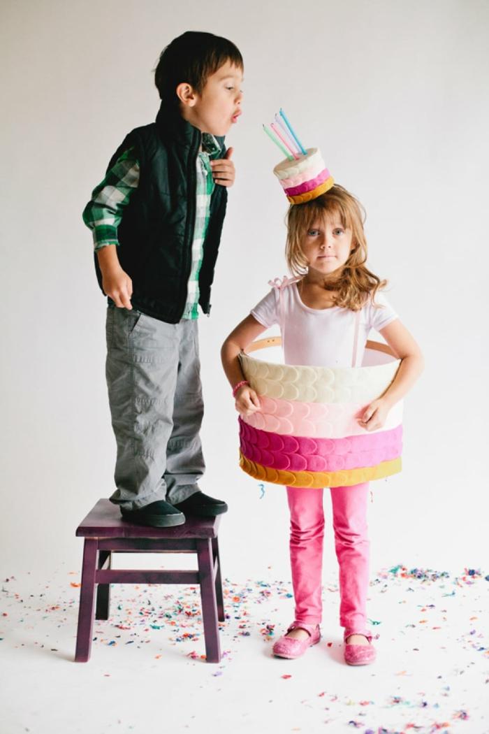 Kinderkostüme Fasching, Geburtstagstorte Kostüm in pink, kleine Torte mit Kerzen als Hut, Junge pustet Kerzen