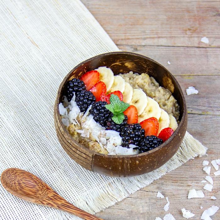 Smoothie Bowl Hirsebrei mit Kokosmilch, Trinkkokosmich und Kokosblütenzucker und Zimt, Erdbeere und Banane, Löffel aus Holz