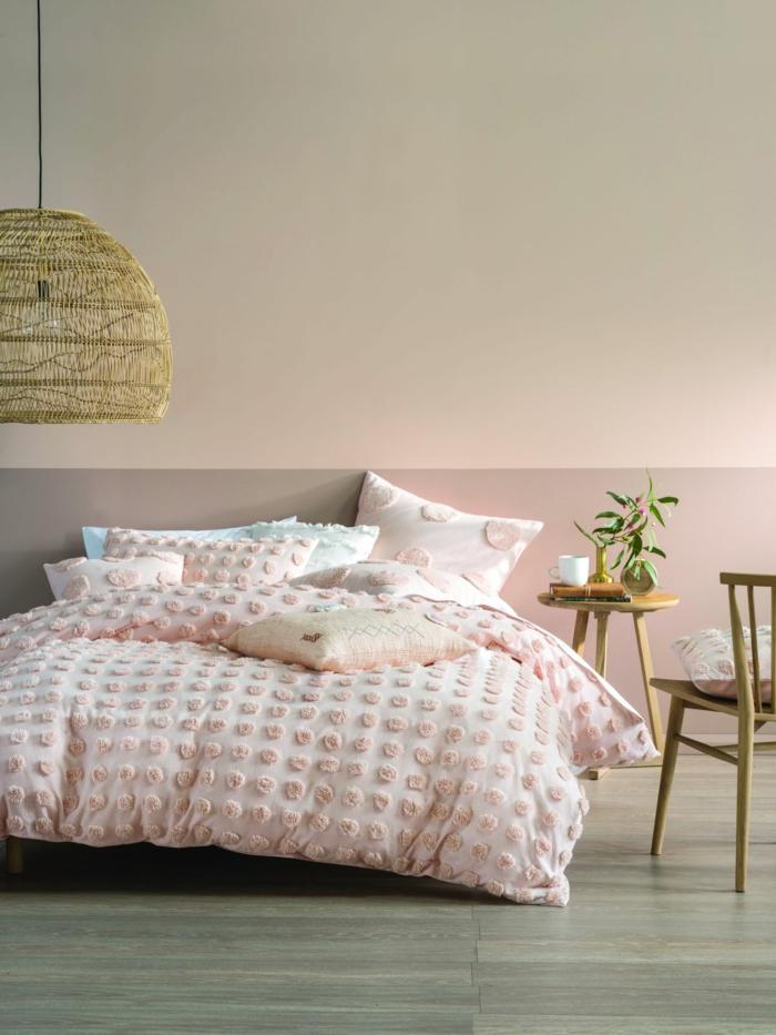 Schlafzimmer rosa grau, Colour-Blocking Wand, großes Bett mit Bettwäsche in rosa Farbe, runder Tisch und Stuhl aus Holz