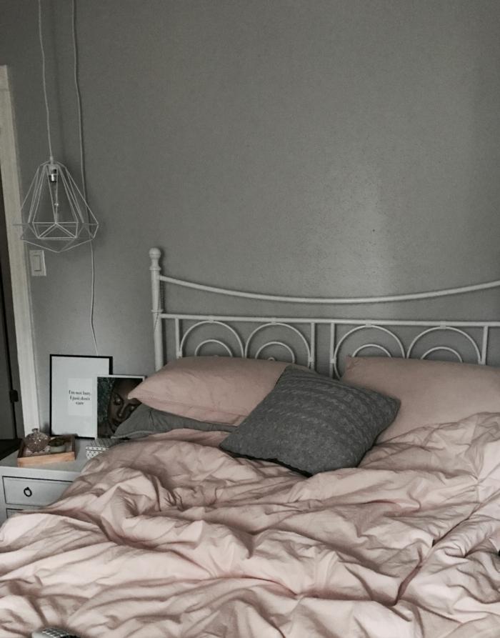Schlafzimmer grau rosa, Bettwäsche in rosa Farbe, großes Bett mit Metallrahmen, Wand bemalt in grau, Pendelleuchte in weiß