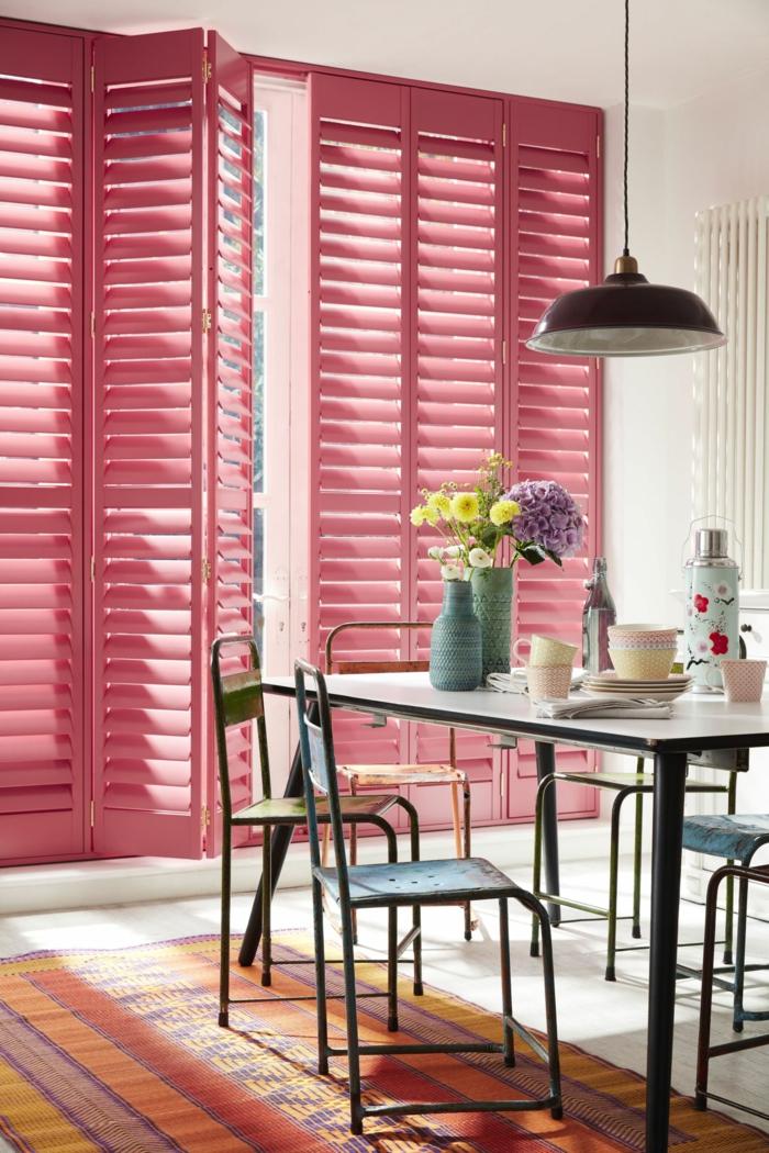 Inneneinrichtung einer kleinen Küche mit Jalousien in pink, kleiner Tisch mit Stühle, bunter Teppich, Aktuelle Wohnraumfarben