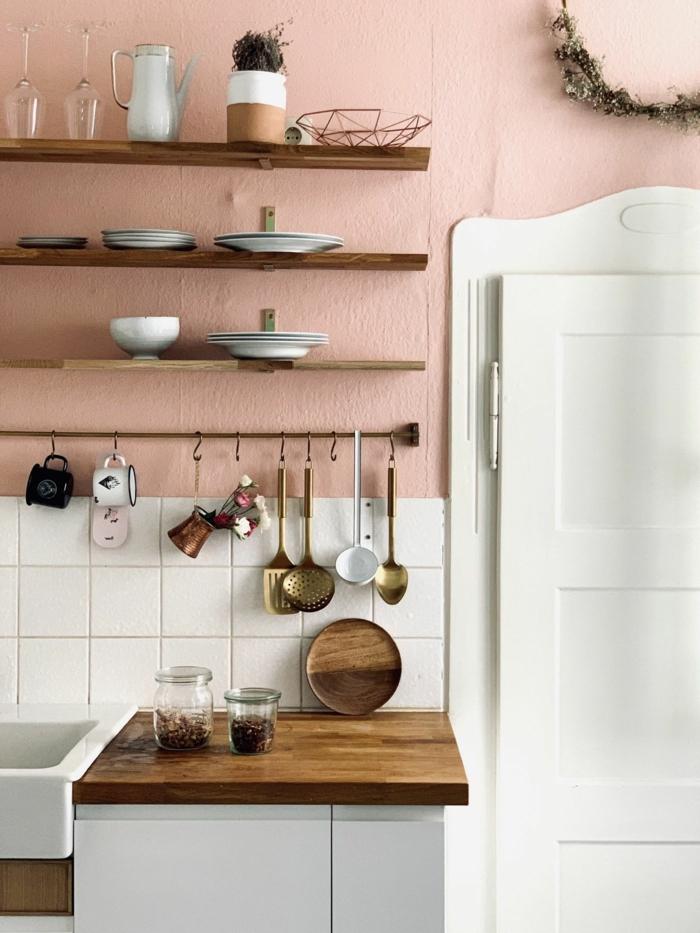 Ausstattung einer Küche in Wandfarbe altrosa und weiße Fliesen, Tischplatte aus Holz, weiße Tür, Wandfarbe Inspiration,