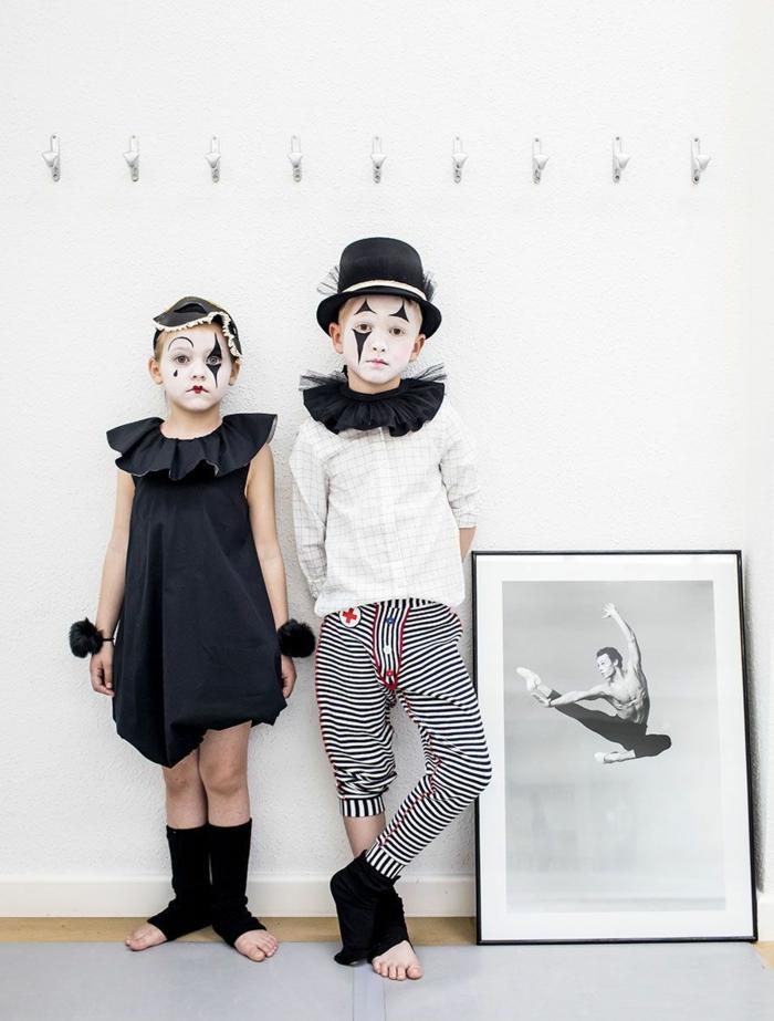 Kinderkostüme Fasching, Arlequino Kostüm, Mädchen im schwarzen Kleid und weiß und schwarz geschminktes Gesicht, Junge in schwarz-weiß karierte Hose und weißes T-Shirt