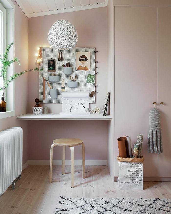 Moderne Farbe für Wand in blass rosa, Einrichtung eines Kinderzimmers, kleiner Kleiderschrank und Schreibtisch, Spielzeuge für Kinder