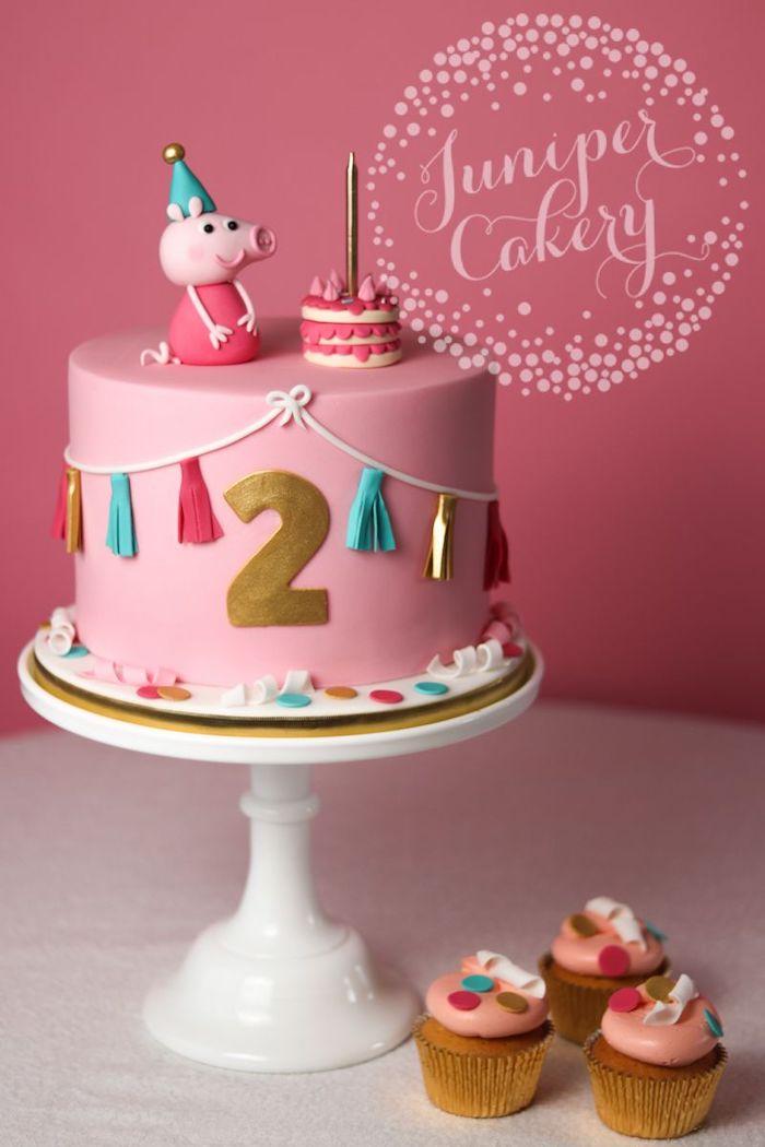 Rosafarbene Fondant Torte mit Peppa Wutz, große goldene Ziffer Zwei, Girlande mit bunten Bommeln, Peppa mit Partyhut und Geburtstagskuchen