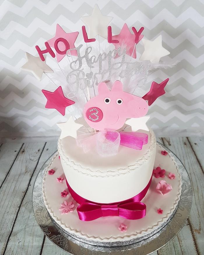 Weiße Fondant Torte mit Peppa Wutz Gesicht, weiße und rosafarbene Sterne an Stäbchen, violette Schleife