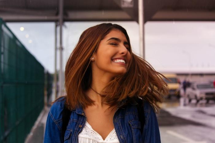 Kurze glatte Haare, lächelnde Frau angezogen im blauen Hemd und weißes Top, Frisuren zaubern mit dem Glätteisen
