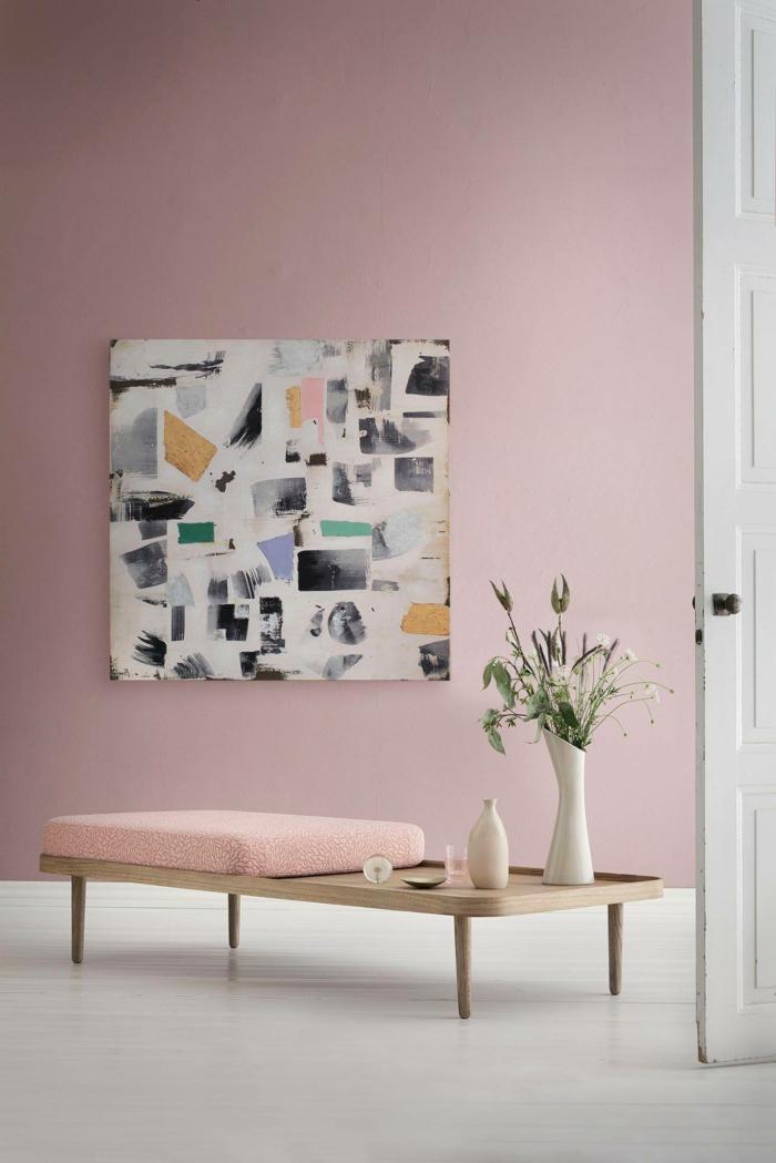 Moderne Ausstattung eines Wohnzimmers mit einem abstrakten Gemälde, niedriger Tisch mit einem Kissen in altrosa, pastell rosa Wandfarbe