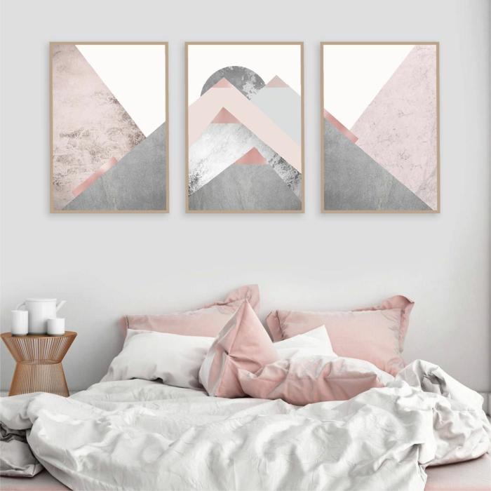 Schlafzimmer grau rosa, drei Bilder mit geometrischen Figuren in grau und rosa, weiße Bettwäsche und rosa Kissen, hellgraue Wand