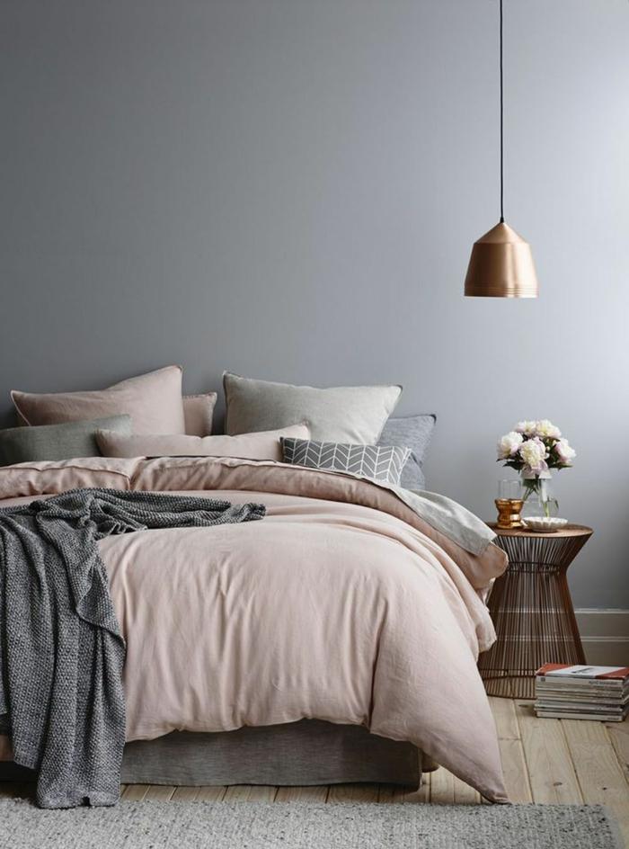 Schlafzimmer rosa grau, Pendelleuchte in gold-rosa Farbe, altrosa Bettwäsche und graue Kissen, Korbtisch mit Blumen obendrauf